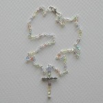 pale beaded cross necklace